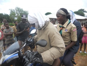 Liberian Scouts demonstrate conveying sick Ebola patient on a bike