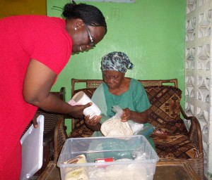 Mother Sarah Doe-Gray viewing the contents of the food package with Rev. Kpaan