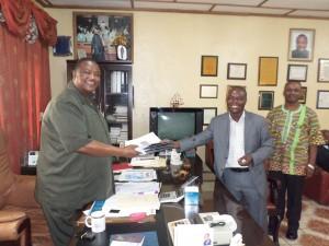 Rev. Dr. Emmanuel Bailey President of United Methodist University UMU receiving the booklets from Edward Harmon Member of the UMC Liberia Publishing Team