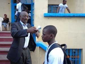 Richard Wiah, President of the College of West Africa (CWA) a United Methodist School checking the temperature of student during the height of the Ebola virus.