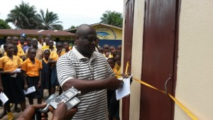 UMC Liberia Connectional Table Director, Rev. George Wilson cutting the ribbon to the modern toilet.