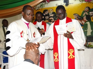 Resident Bishop John Yambasu (standing left) lays hand on Rev Moses Conteh(kneeling) while Connectional Ministry Director Rev Winston Ashcroft (right) helps with microphone.